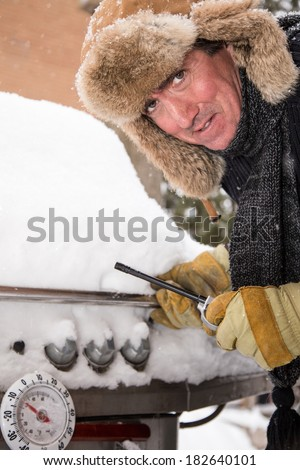 This unhappy griller looks as though he would rather be heading south for a winter vacation than starting his BBQ in the snow - stock photo