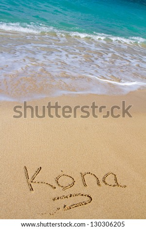 This vacation image shows the word Kona written in the sand with the Ocean water waves coming in to wash the writing away. - stock photo