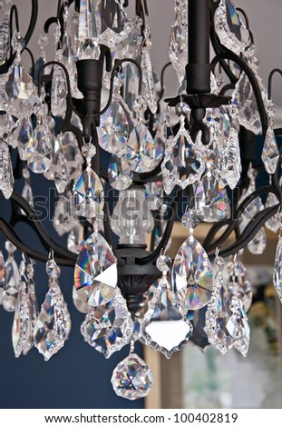 This vertical stock image is a closeup of a beautiful cyrstal chandelier with black wrought iron fixture against a navy blue background interior wall. - stock photo