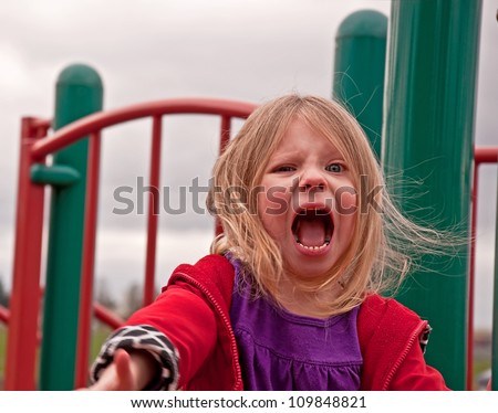 This very angry 4 year old preschool age girl is playing on a playground and is visibly upset.  She's a Caucasian with blond hair and blue eyes, in this highly emotive image.