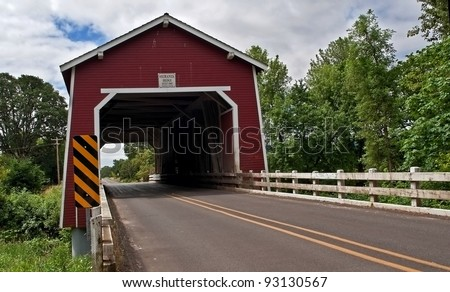 This vintage red covered bridge is a historic landmark in Linn County Oregon.  It's the Shimanek bridge over Thomas Creek built in 1966, the only red colored covered bridge in the region. - stock photo