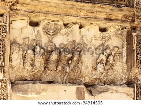 This wall relief on the Arch of Titus reveals Roman soldiers after the destruction of the Temple of Jerusalem in 70 A.D including the Temple Menorah, the Table of the Shewbread and silver trumpets. - stock photo