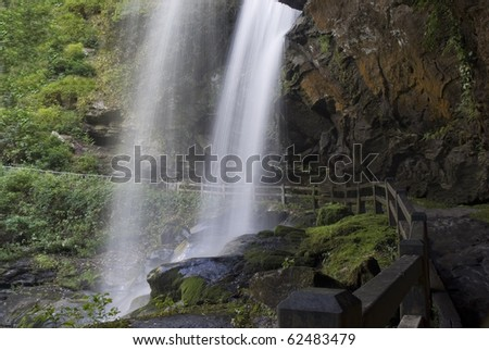 This waterfall is called Dry Falls and is located in North Carolina United States of America. The waterfall is flowing onto the moss covered rocks below. - stock photo