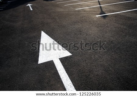 This Way: strong directional / pointing white arrow / roadsign painted on black asphalt. Leadership strategy execution concept. Strategic planning, solution / decision, action plan, guide. Copy space. - stock photo
