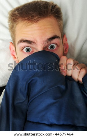This white Caucasian young adult teenage man hides under his blankets and covers because he is scared of the spooky things that go bump in the night. - stock photo
