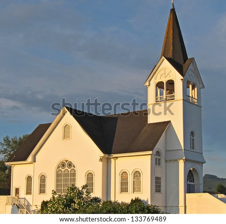 This white church is a historic landmark in Conway, Washington on Fir Island.  Sunset is hitting against a darker sky background. - stock photo
