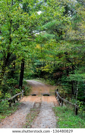 This winding New England road crosses a small stream via a bridge.  It is early fall, with the foliage just beginning to turn, and a light rain has left puddles in the road. - stock photo