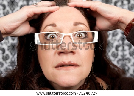 This woman has a crazy look on her face like she is shocked or astounded while holding her hands on her head. - stock photo