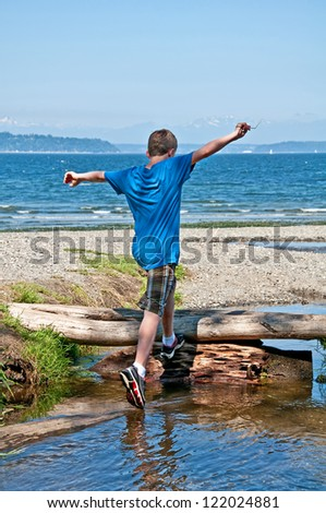 This 13 year old Caucasian boy is running and jumping while playing at the beach.  His arms are held high in the air, ready to conquer the world.  Full body, rear view in vertical format. - stock photo