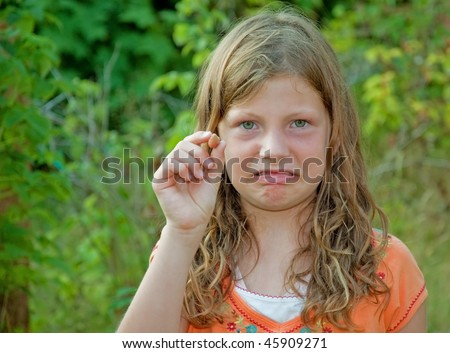 This 8 year old Caucasian girl is making a scowling facial expression over having just picked a rotton raspberry. - stock photo