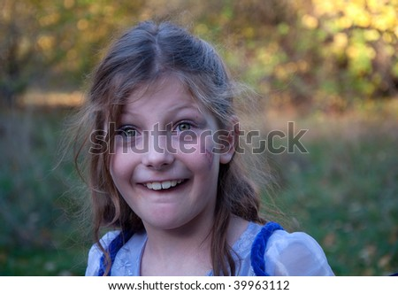 This 9 year old girl is horsing around with play and a goofy facial expression in a carefree childhood moment. - stock photo