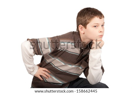 This young boy stands with his hand on his hip and his chin resting on his fist.  - stock photo