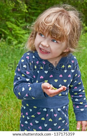 This young girl is playing outside and holding a small green frog in her hand.  She's a bit apprehensive about it.  Model is 3 years old, Caucasian, blond hair and blue eyes. - stock photo
