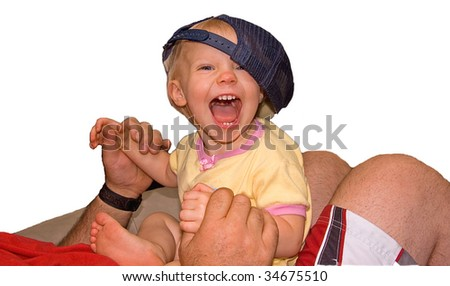 This young girl is yelling and laughing as she's playing on an adult's lap with a baseball cap, against a white background. - stock photo