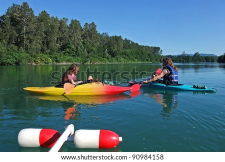 This young mother and daughter are resting while kayaking each in their boats, along a slow, lazy river, enjoying the outdoor recreational sport. - stock photo