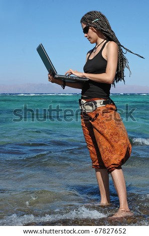 This young woman can be a professional freelancer or a student studying outdoors. She stands on a beach and work at her laptop. - stock photo
