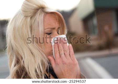 This young woman sneezing into a tissue either has a cold or really bad allergies. - stock photo