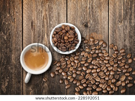 Tho small white coffee cups full of fresh espresso and roasted beans, top view on old wooden table - stock photo