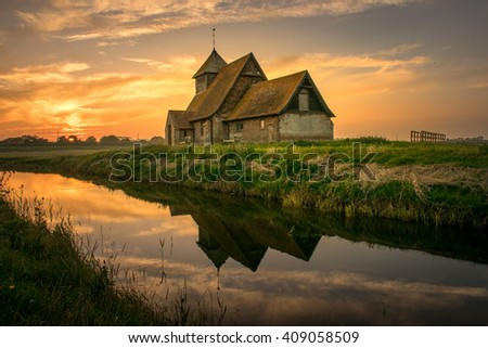 Thomas Becket rural church, Fairfield, Romney marsh, reflected in the river at sunset - stock photo