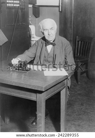 Thomas Edison, seated at desk, demonstrating an old telegraph transmitter in his West Orange, New Jersey, laboratory, 1930. - stock photo
