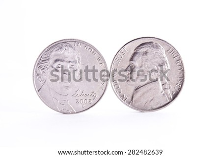 Thomas Jefferson faces on two five cents coins standing on the edge white background  - stock photo