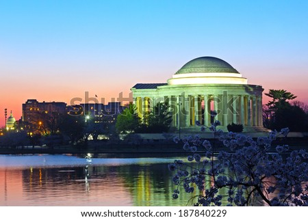 Thomas Jefferson Memorial and Capitol Building at predawn during cherry blossom festival. Landmark reflection in Tidal Basin waters with cherry blooms.