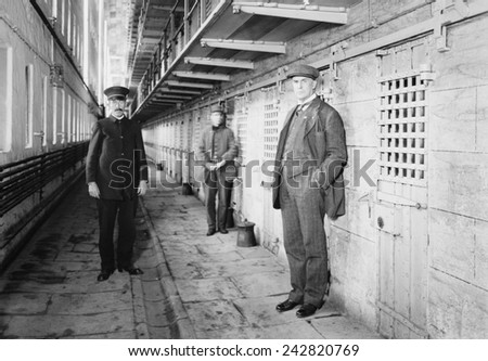 Thomas Mott Osborne (at right), Warden of Sing Sing prison in a cell block with guards. He instituted reform and rehabilitation programs at Sing Sing and later founded Mutual Welfare League. Ca. 1914. - stock photo