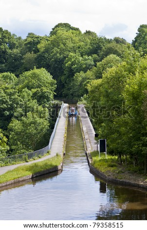 thomas telford's aqueduct carries the llangollen canal across the ceiriog valley at chirk, north wales, uk. Traditional canal narrow boat is crossing.