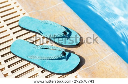 thong sandals shoe behind on a swimming pool close up - stock photo