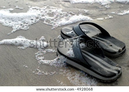 Thongs and Tide - A pair of abandoned black thongs on the sandy shoreline – the happy owner went playing in the waves… - stock photo