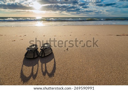 Thongs on the beach against a shoreline. Shallow DOF. - stock photo