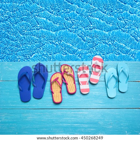 thongs on the blue planks against blue water summer vacation background - stock photo