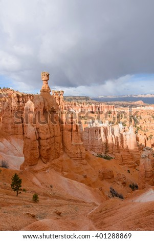 Thor's Hammer - Vertical - Spring storm clouds hanging over towering Thor' Hammer and valley of hoodoo sandstone formations in Bryce Canyon National Park, Utah, USA. - stock photo