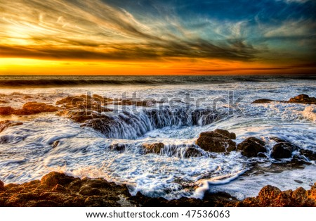 Thor's Well on the central Oregon Coast is a water spout in reverse. Waves crash onto the rocky shelf and the water drains out the hole. This unique feature always amazes me. - stock photo