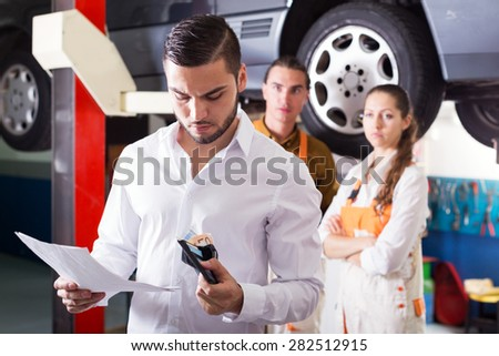 Thoughtful adult client with money at auto repair shop - stock photo