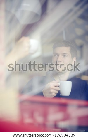 Thoughtful  adult man with coffee cup looking through window in cafe - stock photo