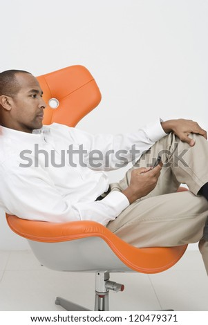 Thoughtful African American businessman holding mobile phone while sitting on chair isolated over white background - stock photo