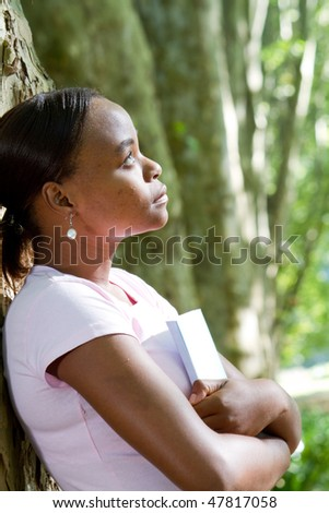 thoughtful african american girl holding books in forest - stock photo