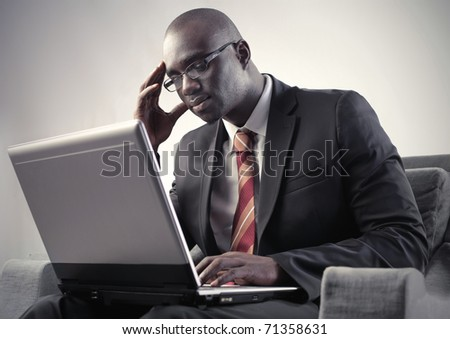 Thoughtful african businessman sitting in front of a laptop - stock photo