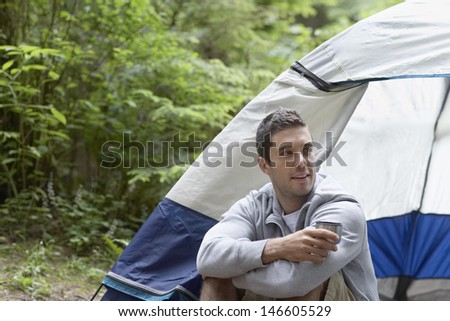 Thoughtful and relaxed young man sitting by tent - stock photo