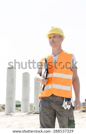 Thoughtful architect looking away while holding clipboard at construction site - stock photo