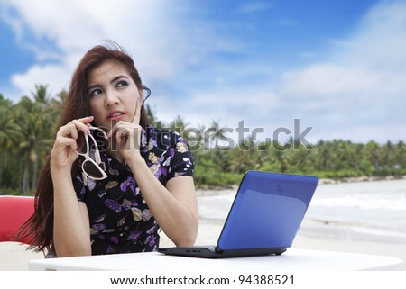 Thoughtful asian businesswoman on the beach - stock photo