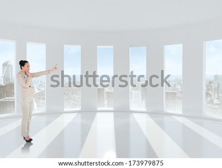 Thoughtful asian businesswoman pointing against bright white room with windows