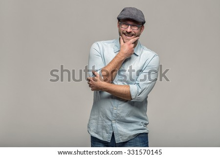Thoughtful attractive middle-aged man with his finger to his mouth standing looking towards the camera on a grey background - stock photo