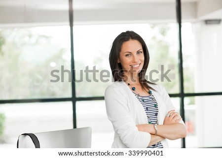 Thoughtful attractive woman standing with arms crossed on chest - stock photo