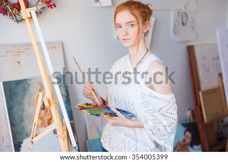 Thoughtful attractive young female painter using oil paints for painting on canvas in art workshop - stock photo