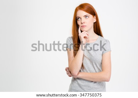 Thoughtful attractive young female with long red hair thinking and looking away over white background - stock photo