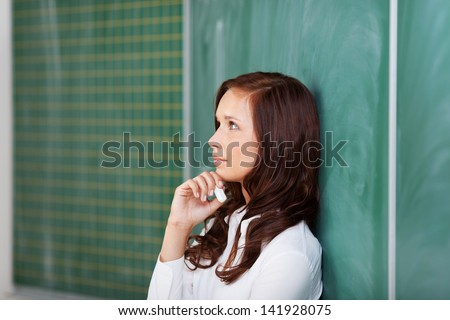 Thoughtful attractive young teacher leaning against a blank chalkboard with a piece of chalk held in her hand - stock photo