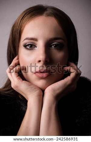 Thoughtful attractive young woman staring at the camera with her chin resting on her hands and a solemn serious expression, close up head and shoulders