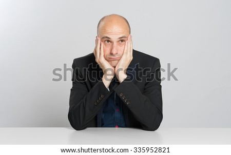 thoughtful bald businessman sits at the table - stock photo